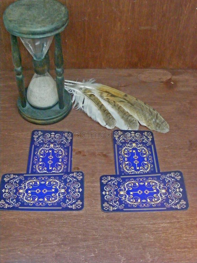 与猫头鹰羽毛的在破旧的桌上的占卜用的纸牌和滴漏 库存照片