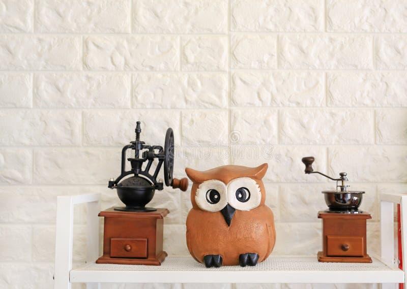 与猫头鹰雕象的磨咖啡器反对砖墙背景 不睡觉象猫头鹰概念 免版税库存图片