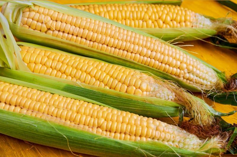 与玉米叶子的新鲜的玉米棒子在黄色表面关闭 免版税库存照片