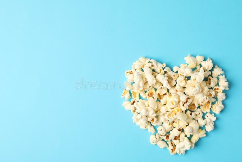与玉米花心脏的平的被放置的构成在蓝色背景 库存照片