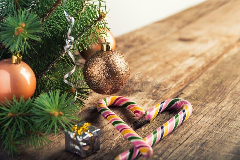 与玩具、焦糖藤茎和星的圣诞树在葡萄酒样式的黑暗的木和白色背景 文本的空间 愉快的新的y 免版税库存图片