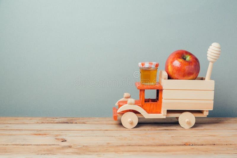 与玩具卡车、蜂蜜和苹果的犹太假日Rosh Hashana背景 免版税库存图片