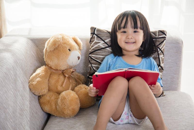 与玩具熊的微笑的亚洲中国小女孩阅读书 库存图片
