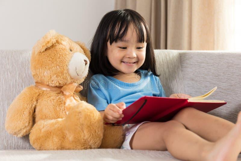 与玩具熊的微笑的亚洲中国小女孩阅读书 免版税图库摄影