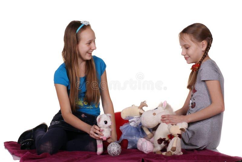 与玩具的两个女孩戏剧 库存图片