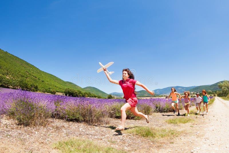 与玩具飞机和孩子的女孩奔跑设法捉住她 库存照片