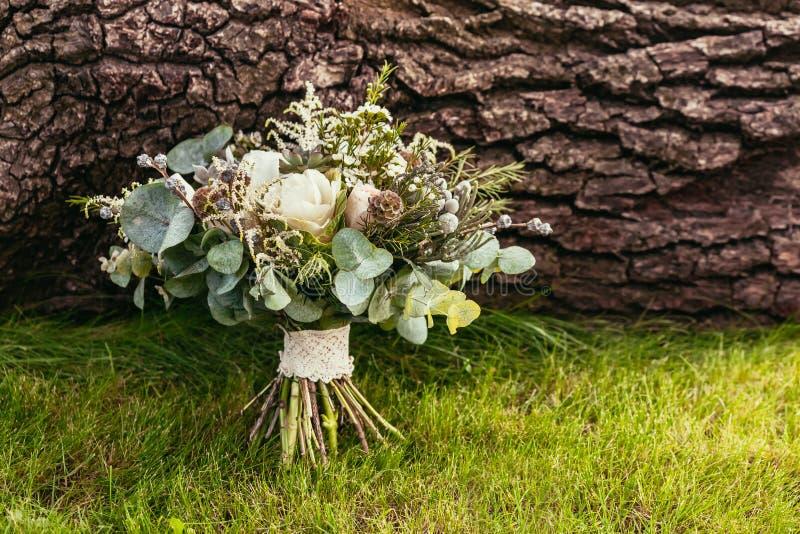 与玫瑰和其他花的婚礼花束在绿草和 免版税库存图片