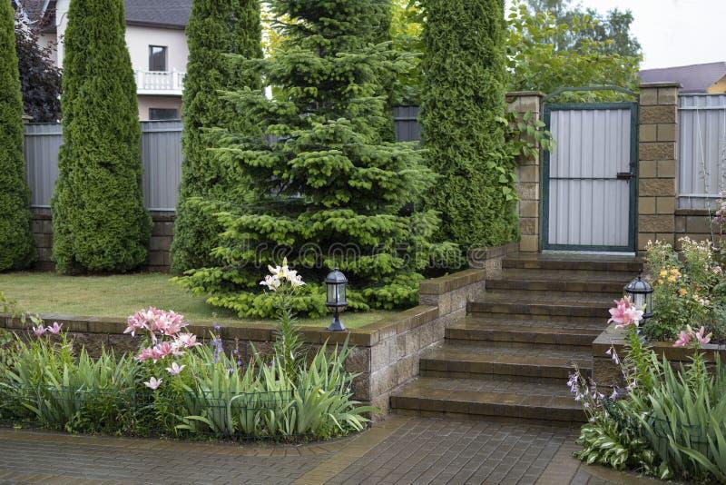 与玫瑰和百合一个穿着考究的花圃的风景设计与野兔和猬的雕塑和 图库摄影