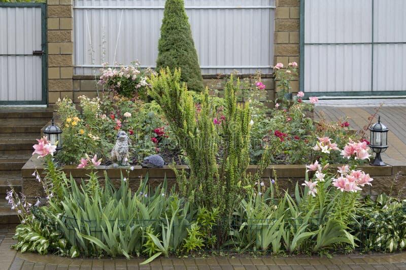 与玫瑰和百合一个穿着考究的花圃的风景设计与野兔和猬的雕塑 免版税库存图片
