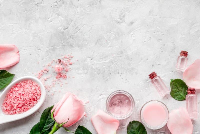 与玫瑰油的自然有机化妆用品 奶油,化妆水,在灰色背景顶视图copyspace的温泉盐 库存照片