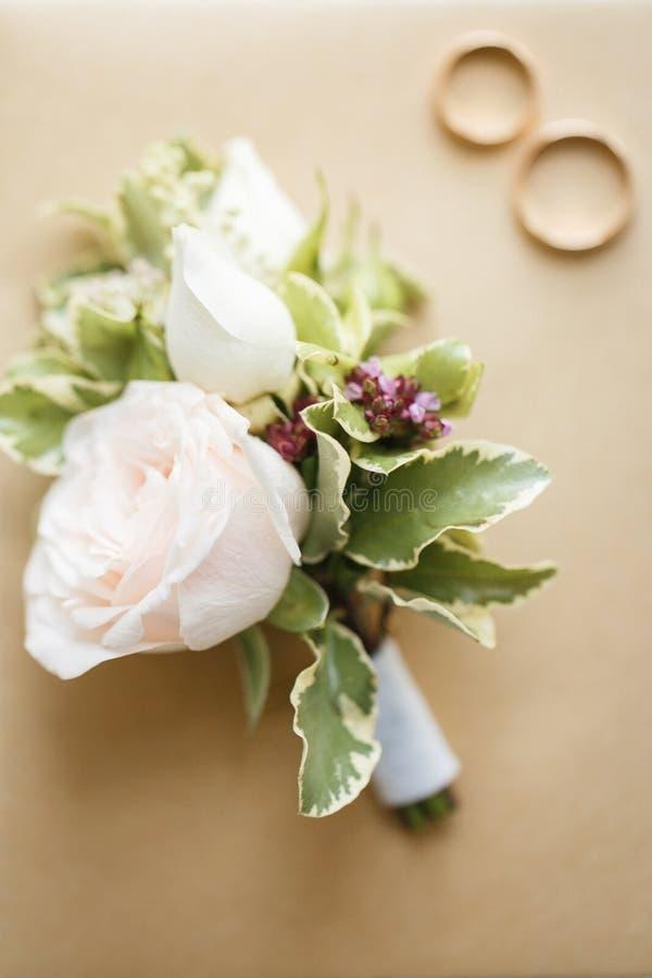 与玫瑰的新郎的钮扣眼上插的花 免版税库存照片