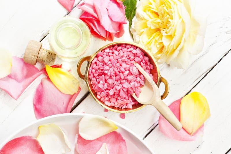 与玫瑰的温泉设置,在碗,按摩油的腌制槽用食盐 免版税库存图片
