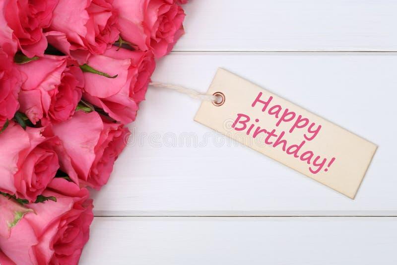 与玫瑰的生日快乐开花与在木的贺卡 免版税库存图片