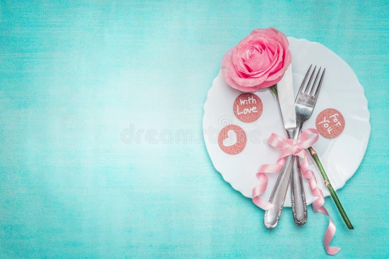 与玫瑰色的浪漫饭桌餐位餐具和签署在蓝色背景,顶视图的装饰 库存照片