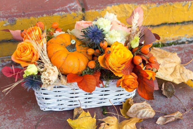 与玫瑰色花、秋天叶子和南瓜的美丽的秋天万圣夜花束在篮子 免版税库存图片