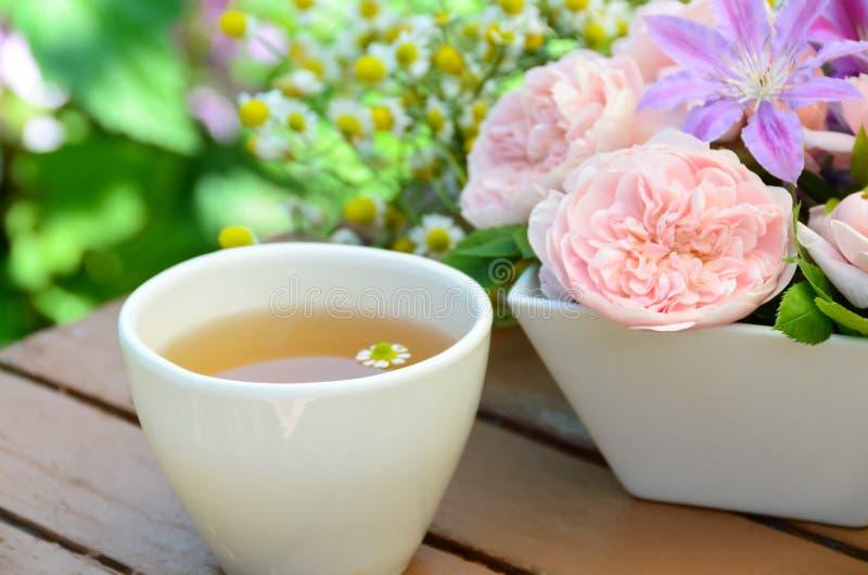 与玫瑰色花的小休在庭院里 免版税库存照片
