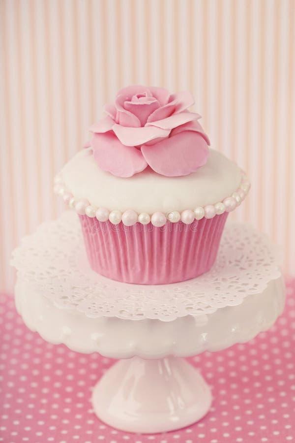 与玫瑰色花的杯形蛋糕 免版税库存图片