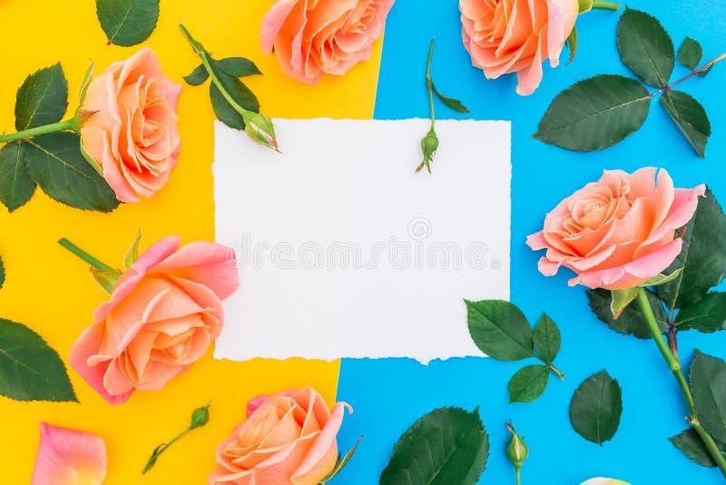 与玫瑰花和绿色的花卉样式在黄色和蓝色背景离开 平的位置,顶视图 与纸的花背景 图库摄影
