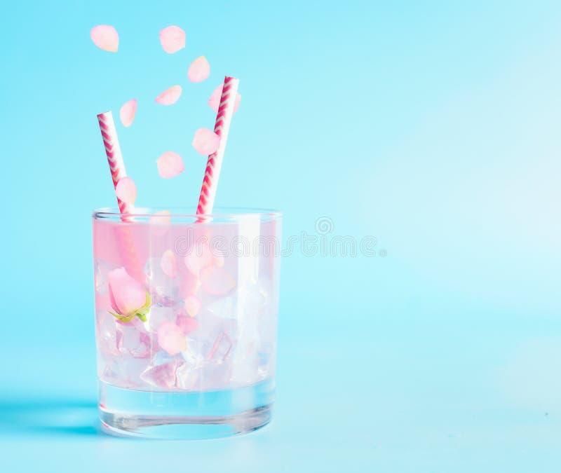 与玫瑰花瓣和花的夏天饮料 茶点饮料 被冰的柠檬水或鸡尾酒在蓝色背景 免版税库存照片