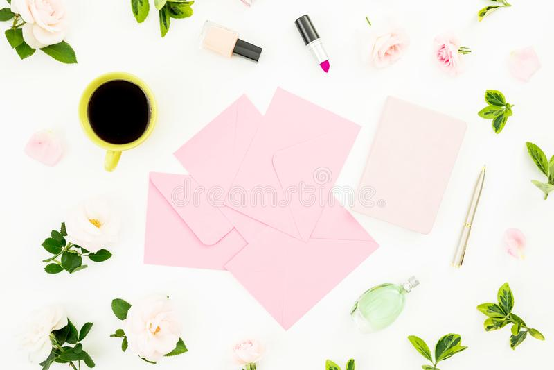 与玫瑰花,纸牌、笔记本、化妆用品和咖啡杯的女性构成在白色背景 平的位置,顶视图 库存图片