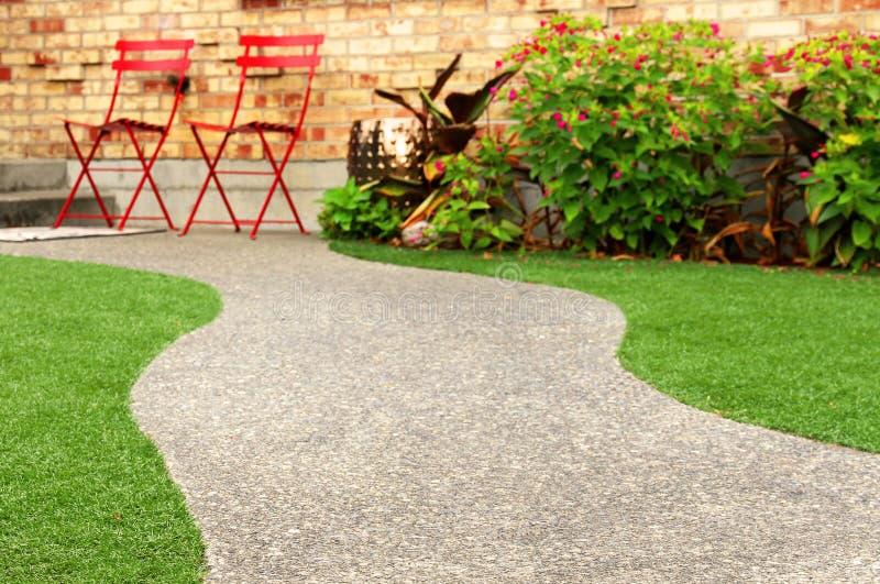 与环境美化与人为草的完善的草的步行方式在住宅区 免版税库存图片