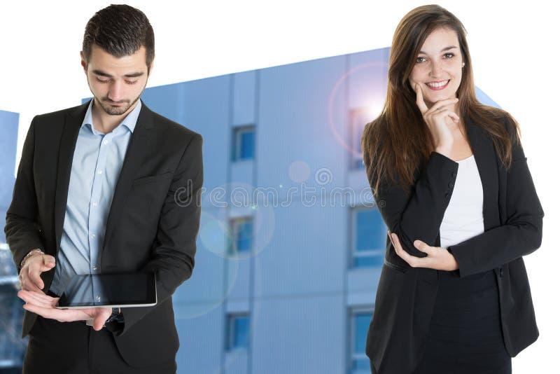 与现代办公室片剂前面的商人和女实业家不动产一个大塔的 免版税库存图片