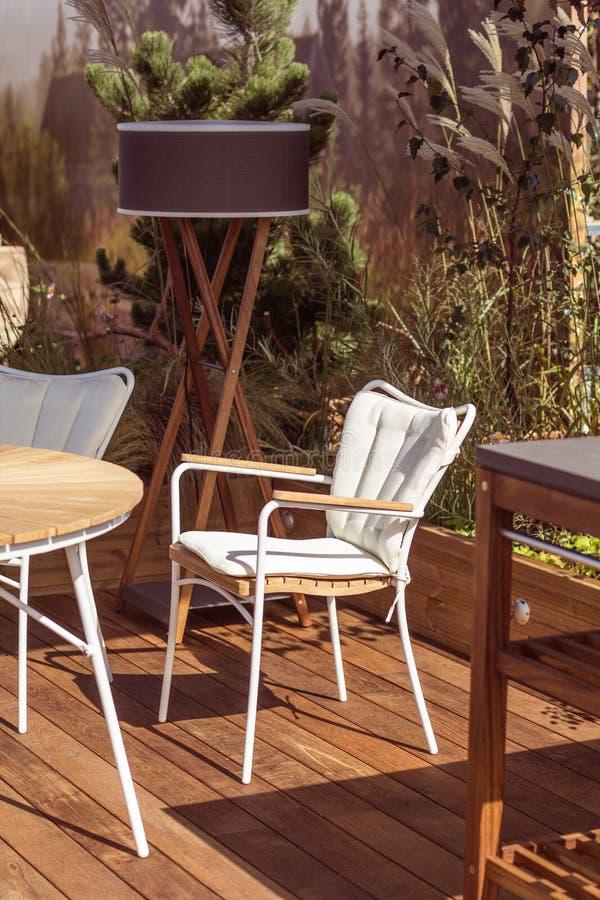 与现代家具和自然设计的豪华大阳台 在木地板和美丽的植物上的白色椅子 免版税库存照片