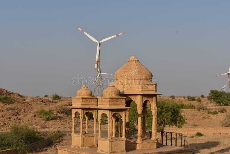 与现代风车的古老纪念碑在bada baag Jaisalmer拉贾斯坦印度 免版税库存图片
