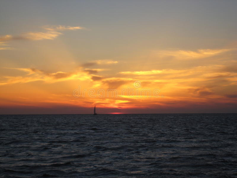 与现出轮廓的小船的日落 库存图片