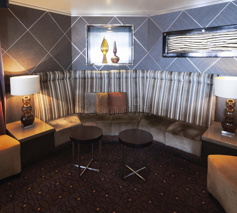 与现代和时髦的设计的内部与与坐垫和低当代椅子的沙发角落 免版税库存图片
