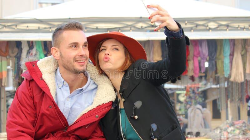 与现代智能手机的年轻夫妇作为selfie 免版税图库摄影