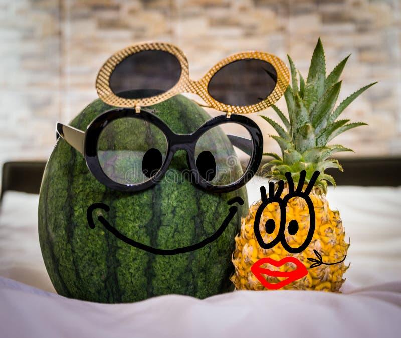 与玻璃和女孩菠萝的男孩西瓜与红色嘴唇在床上 滑稽的图片,获得的夫妇乐趣 免版税库存照片