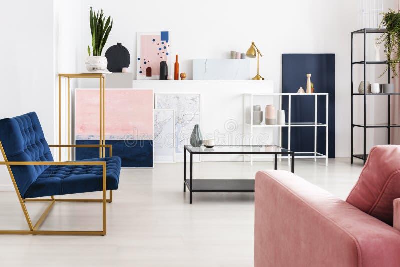 与玻璃桌面的咖啡桌在现代有很多有汽油蓝色扶手椅子的,粉末桃红色颜色客厅中间 免版税库存照片