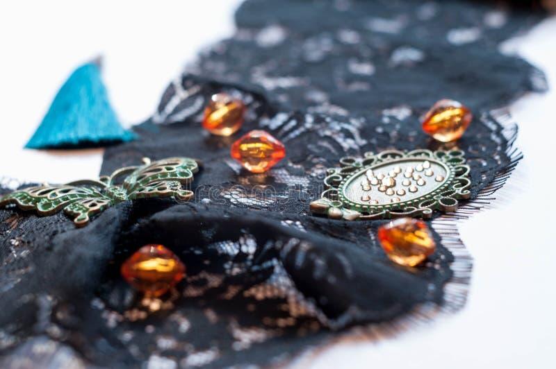 与玻璃橙色小珠、绿色小框架、假钻石、装饰蝴蝶和蓝色缨子的黑装饰品鞋带 免版税库存图片