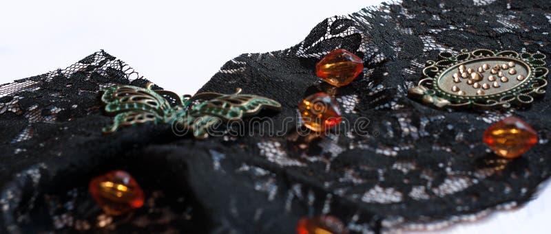 与玻璃橙色小珠、绿色小框架、假钻石、装饰蝴蝶和蓝色缨子的黑装饰品鞋带 库存照片