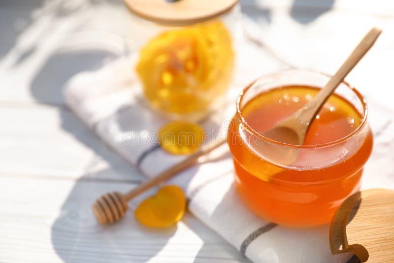 与玻璃瓶子的构成在白色木桌上的新鲜的玫瑰色蜂蜜 图库摄影