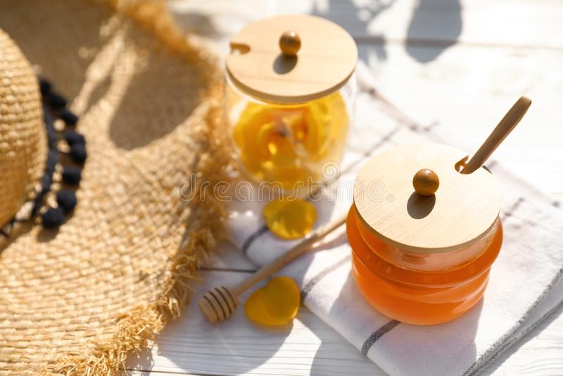 与玻璃瓶子的构成在白色木桌上的新鲜的玫瑰色蜂蜜 库存图片