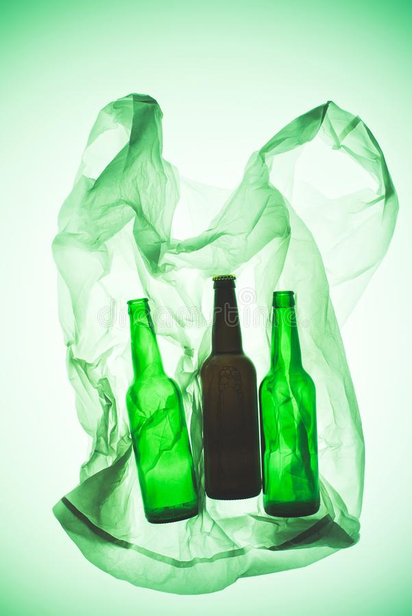 与玻璃瓶的透明塑料袋在绿色被定调子的光下 免版税库存照片