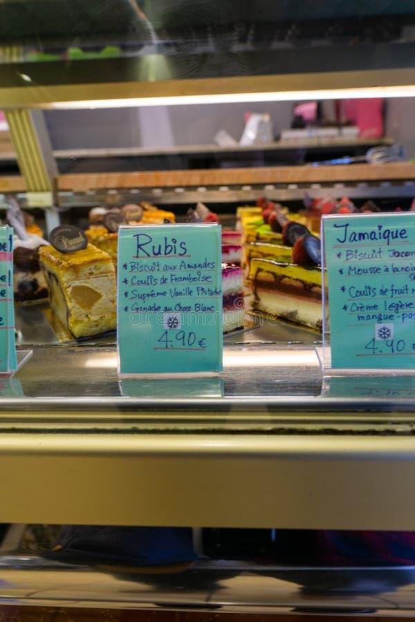 与玻璃的价格的蛋糕在糖果店的 免版税图库摄影