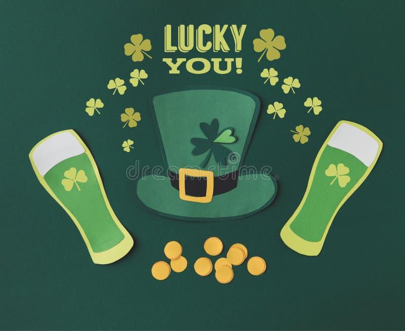 与玻璃的平的位置啤酒、硬币、绿色帽子,三叶草和幸运您字法 库存照片