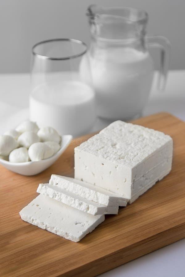与玻璃的被切的新鲜的白色乳酪和无盐干酪球与mlk 库存图片
