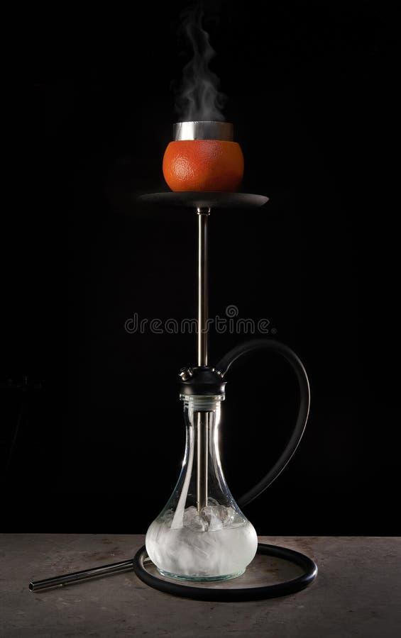 与玻璃碗和葡萄柚芳香的现代水烟筒在黑背景 库存照片