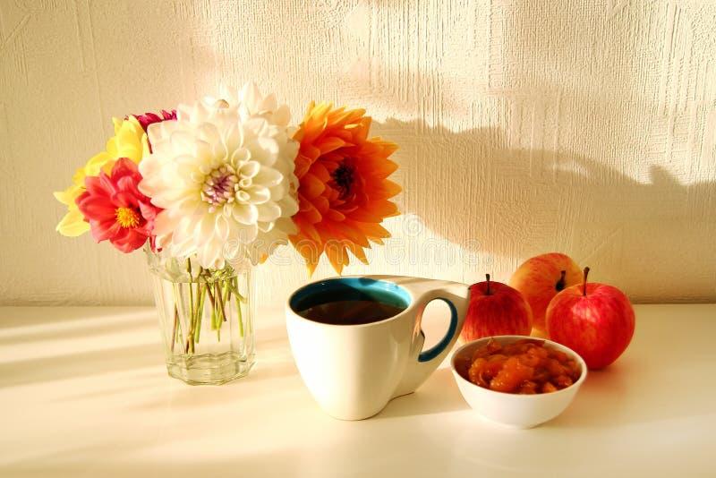 与玻璃花瓶的静物画有牡丹、茶,苹果果酱和苹果五颜六色的花的在白色桌上 库存照片