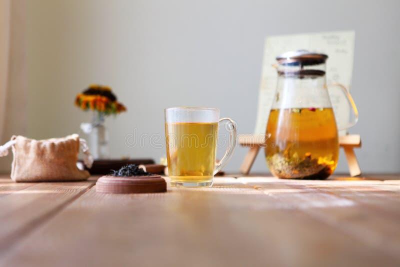 与玻璃茶壶,杯子,干玫瑰色芽的传统heral茶 在家木桌上的花,阳光背景 免版税库存图片