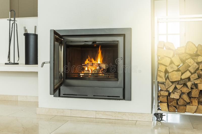 与玻璃门,在黄色大理石地板家内部的白色墙壁的豪华现代设计壁炉 图库摄影
