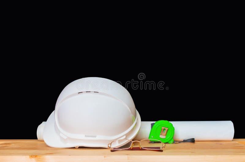 与玻璃,纸卷计划图纸和测量的磁带概念建筑的盔甲塑料白色木的 库存图片
