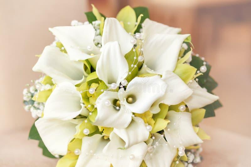 与珍珠、兰花和水芋属的婚礼花束 免版税图库摄影