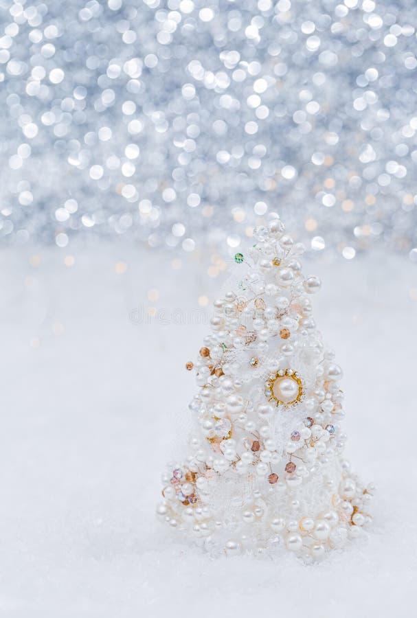 与珍珠和小珠的白色圣诞节快乐树在美好的被弄脏的bokeh背景和发光的诗歌选旁边的雪 r 库存图片