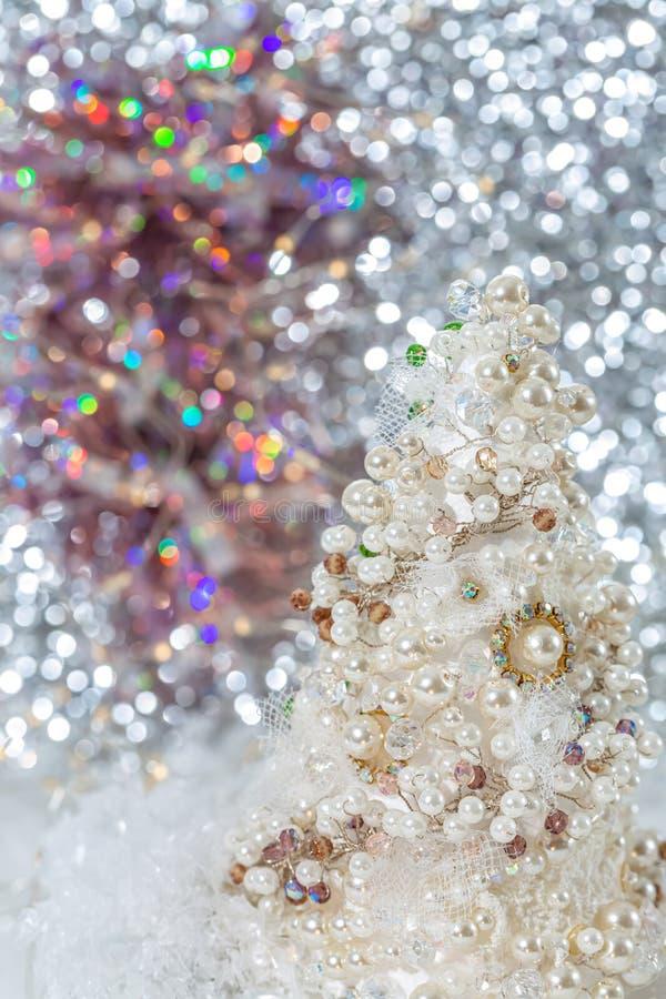 与珍珠和小珠的白色圣诞节快乐树在美好的被弄脏的bokeh背景和发光的诗歌选旁边的雪 r 免版税库存照片