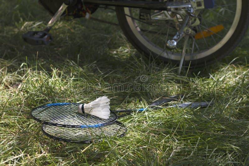 与球拍的白色shuttlecock在电自行车绿草和轮子在背景的 免版税库存图片